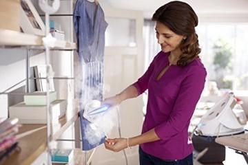 Frau am bügeln mit der Frau am Kleiderschrank mit dem Philips PerfectCare Elite Silence GC9640/60 Dampfbügelstation
