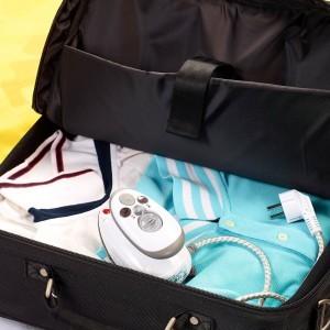 Koffer mit Gepäck und Reise Bügeleisen